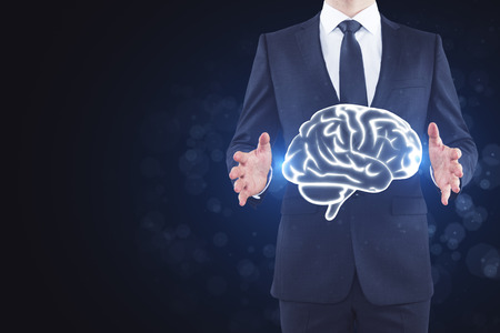Businessman holding abstract brain hologram on blurry background. Brainstorm and mind concept  Zdjęcie Seryjne