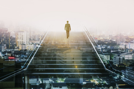 Businessman climbing stairs on abstract city background with sunlight. Success and employment concept. Double exposure