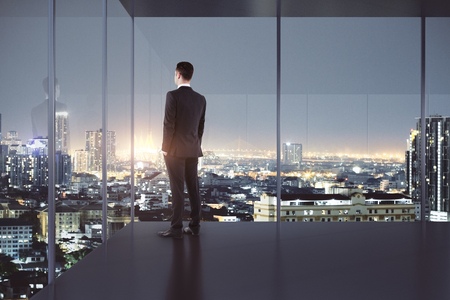 Young businessman looking out of window in modern office interior with night city view. 3D Rendering  Stock Photo