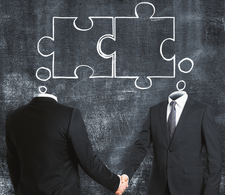 Businessmen shaking hands on concrete wall background with joint puzzle sketch. Teamwork and partnership concept