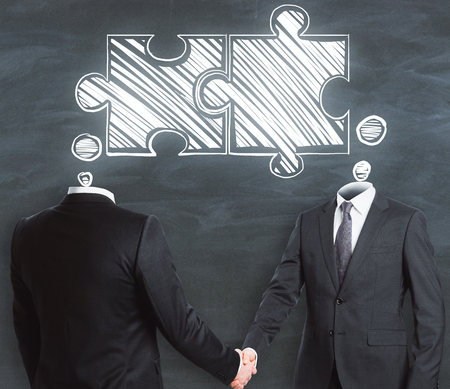 Businessmen shaking hands on chalkboard wall background with joint puzzle sketch. Teamwork and partners concept  Stok Fotoğraf