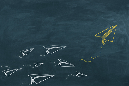 Chalkboard background with drawn paper planes. Leadership and startup concept