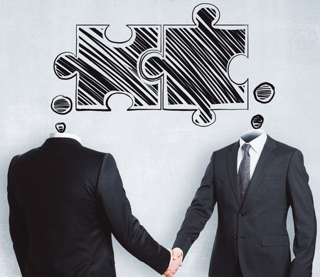 Puzzle headed businessmen shaking hands on concrete background. Teamwork and success concept