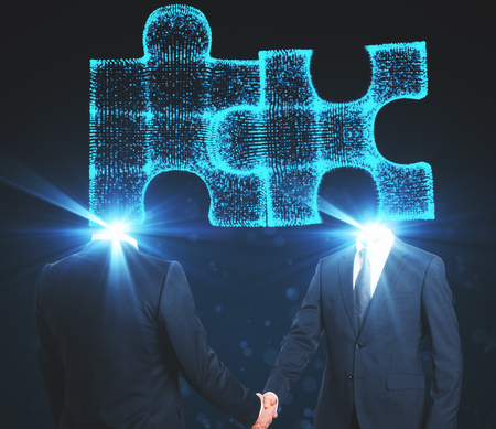 Puzzle headed businessmen shaking hands on blue backdrop. Teamwork and success concept Reklamní fotografie