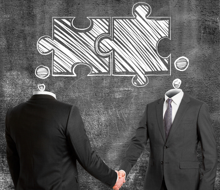 Businessmen shaking hands on concrete wall background with joint puzzle sketch. Teamwork and colleagues concept Stok Fotoğraf - 97710532