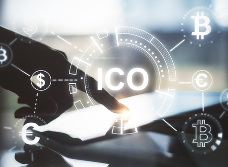 Hand using touchpad with abstract ICO hologram. Initial coin offering concept. Double exposure