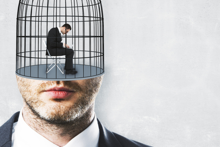 Cage headed businessman on concrete wall background with copyspace. Freedom and innovation concept