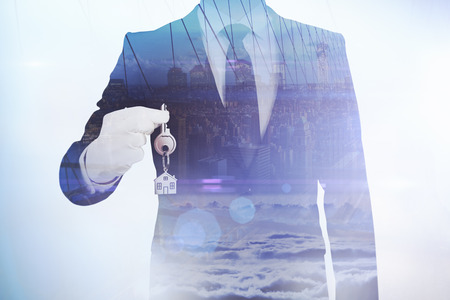 Businesman holding key on abstract city background. Real estate concept. Double exposure