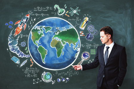 Handsome european businessman drawing creative globe sketch on chalkboard backdrop. Science and world concept