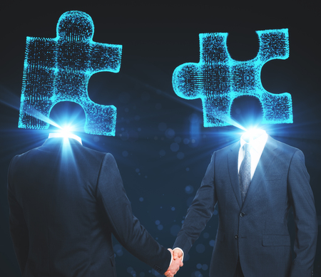 Puzzle headed businessmen shaking hands on blue background. Partnership and success concept Reklamní fotografie
