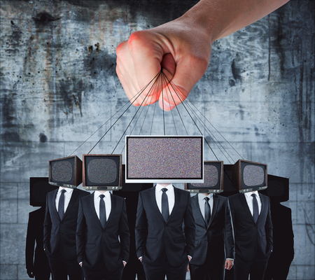 Hand holding TV headed businessmen on rope. Manipulation and brainwash concept