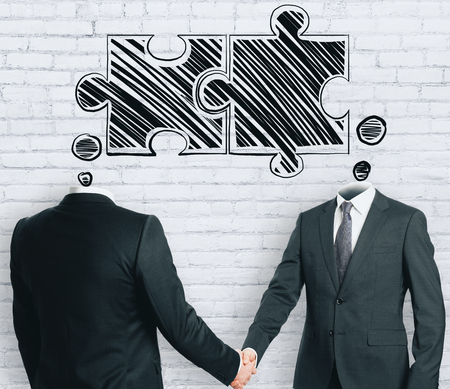 Puzzle headed businessmen shaking hands on brick background. Teamwork and success concept