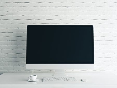 Close up of creative designer desktop with blank computer monitor, coffee cup and keyboard on white brick wall background. Mock up, 3D Rendering  Stock Photo
