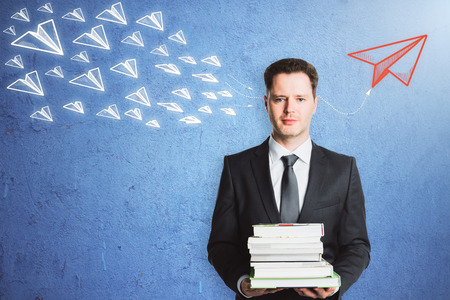 Businessman with books standing on concrete wall background with drawn paper planes. Leadership and success concept