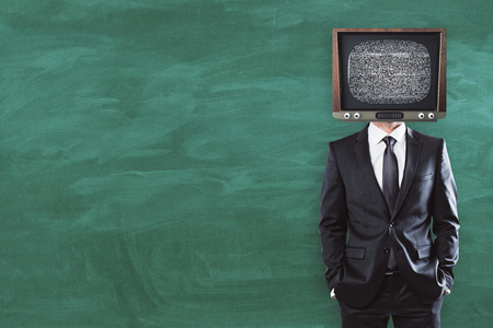 TV headed businessman standing on chalkboard background with copy space Stock Photo