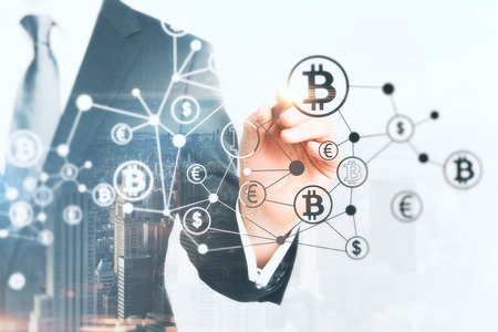 Businessman drawing creative bitcoin hologram on abstract city background. Cryptography and finance concept. Double exposure