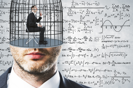 Cage headed businessman on concrete wall background with mathematical formulas. Freedom and science concept  Reklamní fotografie