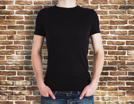 Man wearing empty black shirt on brick wall background. Advertisement and design concept. Mock up