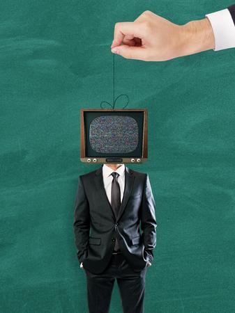 Hand holding TV headed businessman on rope. Chalkboard background. Manipulation concept
