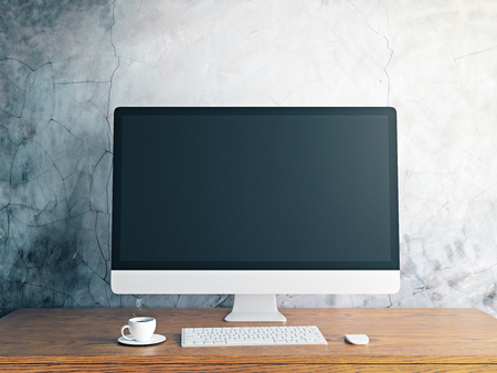 Close up of creative designer desktop with blank computer screen, coffee cup and keyboard on concrete wall background. Mock up, 3D Rendering