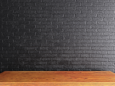 Empty wooden desk on black brick wall background. Mock up, 3D Rendering