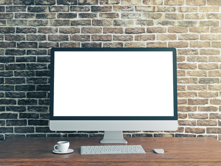 Close up of creative designer desktop with empty white computer screen, coffee cup and keyboard on textured brick wall background. Mock up, 3D Rendering