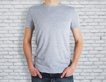 Man wearing empty grey shirt on brick wall background. Advertisement and design concept. Mock up