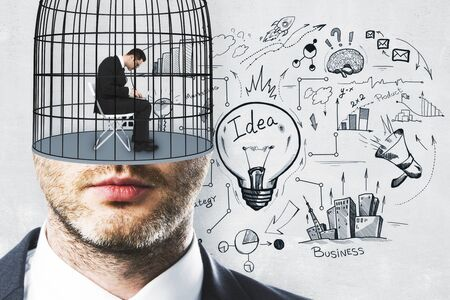 Cage headed businessman on concrete wall background with business sketch. Freedom and plan concept