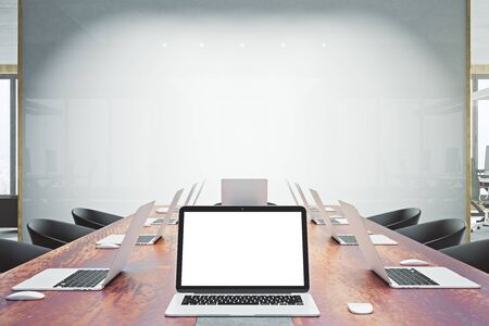 Close up of empty white laptop in wooden conference table. Whiteboard in the background. Presentation concept. Mock up, 3D Rendering  Stock Photo