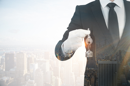 Businessman holding key on abstract city background. Real estate and mortgage concept. Double exposure  Stok Fotoğraf