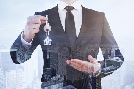 Businessman holding key on abstract city background. Real estate concept. Double exposure