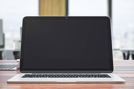 Front view of blank laptop computer screen on office interior background with daylight. Mock up, 3D Rendering  Stock Photo