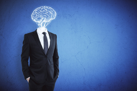 Brain headed businessman on blue concrete wall background. Brainstorm and success concept Stock Photo