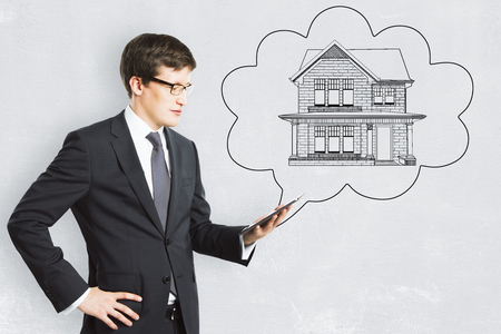 Young european businessman with abstract house sketch in thought cloud drawn on concrete background. Housing, real estate and think concept