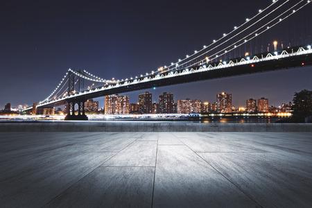 Creative night city background with empty concrete ground Standard-Bild