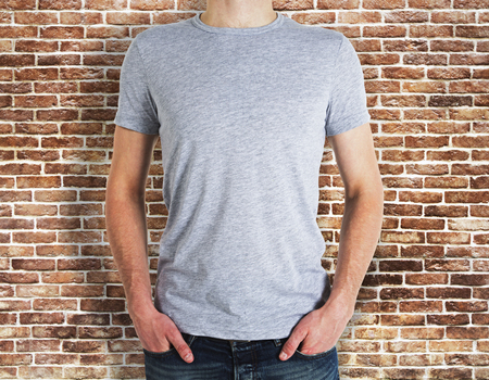 Man wearing empty grey t-shirt on brick wall background. Advertisement and design concept. Mock up