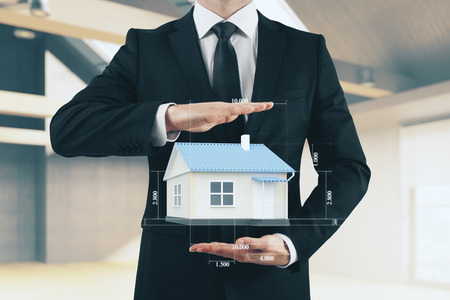 Businessman holding creative house blueprint on blurry office interior background. Architect and rent concept