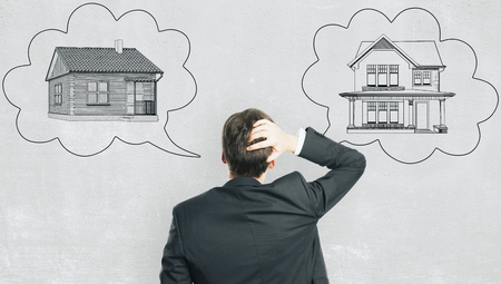 Back view of pensive young european businessman with abstract house sketch in thought cloud drawn on concrete wall background. Housing, real estate and choose concept