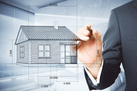 Businessman hand drawing creative house blueprint on blurry office interior background. Architect and industry concept