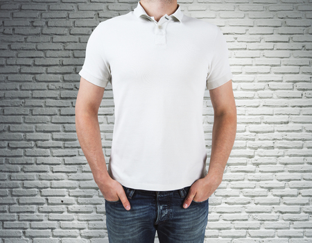 Man wearing clean white shirt on brick wall background. Advertisement and design concept. Mock up Stock Photo