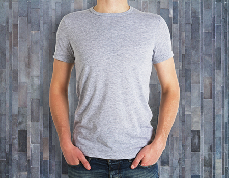 Man wearing clean shirt on wooden wall background. Advertisement and design concept. Mock up