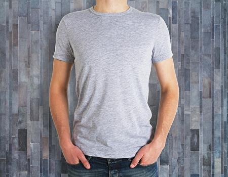 Uomo che indossa una camicia pulita sulla parete in legno dello sfondo. Pubblicità e concetto di design. Modello Archivio Fotografico