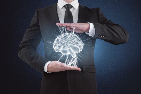 Businessman hand holding digital brain on blue background. Science and medical concept