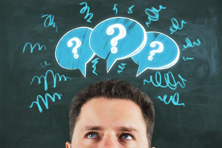 Young businessman with drawn question marks. Brainstorm and choice concept Stockfoto