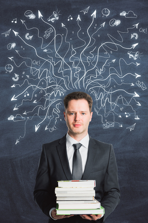 Businessman holding books on abstract chalkboard background with drawin arrows. Choice and education concept  Stock fotó