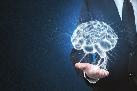 Businessman hand holding digital brain on blue background. Science and medicine concept Stockfoto - 100957196