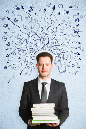 Businessman holding books on abstract concrete background with drawin arrows. Choice and education concept  Фото со стока