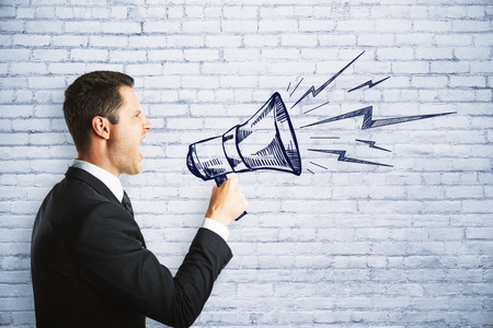 Side vew of handsome young european businessman screaming into megaphone on brick background. Communication and message concept