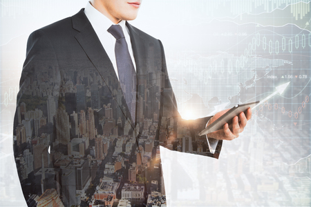 European businessman using tablet on abstract city background with forex chart. Finance and investment concept. Double exposure