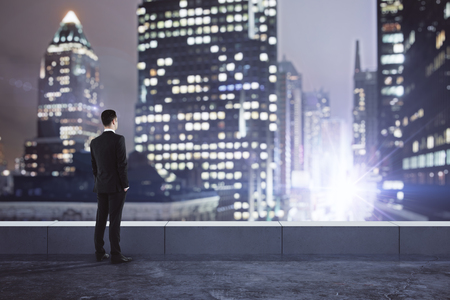 Businessman looking at glowing blurry night city from rooftop. Research concept
